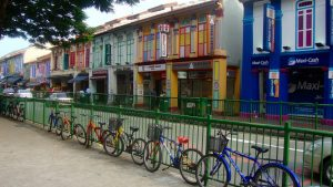 Colorful row of buildings with bikes parked in front of a green fence