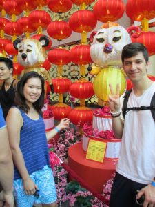Max holding up two fingers in a peace sign standing next to a display in Singapore with a friend