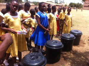 The four teams of students standing with their own composting bin